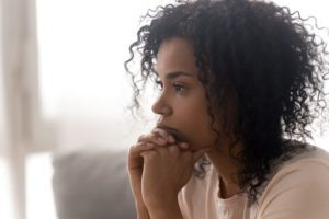 a woman staring off into the distance with her hands folded against her chin