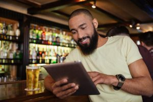African american man drinking beer in pub and using tablet