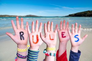 Children Hands Building Colorful Word Rules. Ocean And Beach As Background