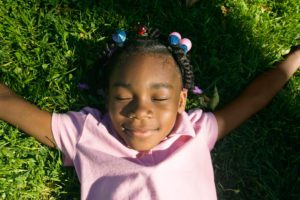An African American girl, laying with her eyes closed and her arms outstretched in the grass