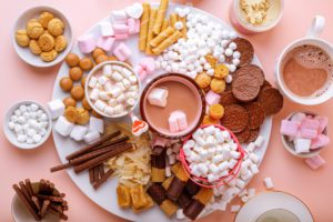 Hot chocolate, marshmallows, chocolates and cookies charcuterie board on pink background. Closeup view, horizontal orientation