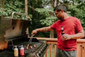 man grilling while drinking a beer on father's day