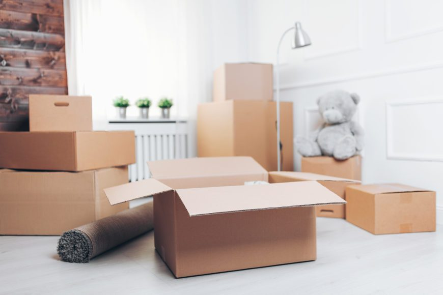 Moving concept. Room full of cardboard boxes for a new mom in town