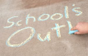 School's Out! written in yellow and blue chalk on cement