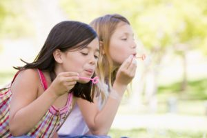 two girls blowing bubbles outside