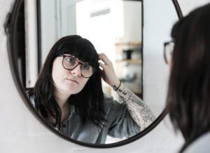 a mom with dark hair and glasses peering at herself in the mirror who needs to be reminded that she is enough