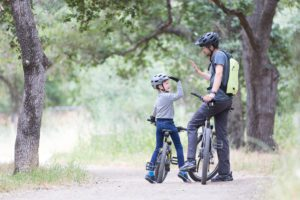 a father and son riding bikes on a trail