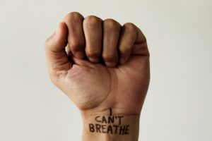 closeup of the raised fist of a man with the text I cant breathe on his wrist, as it is used as slogan in the George Floyd protests in response to police brutality and racism in the United States