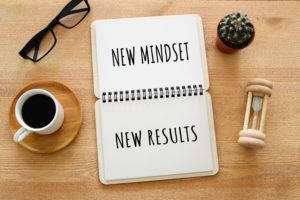 top view image of table with open notebook and the text new mindset new results. success and personal development concept to level up
