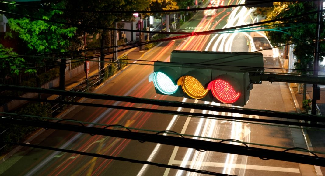 horizontal stop light at night with red, yellow, and green illuminated