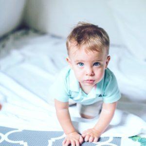 Anxious toddler crawling on white blanket