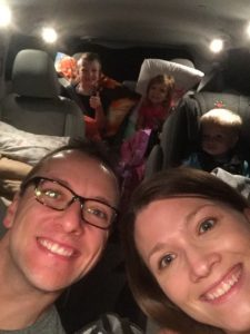 family selfie inside of packed minivan