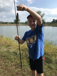 boy holding fish caught while fishing in front of lake