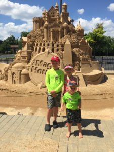 kids pose in front of giant sandcastle at The Magic House in St. Louis