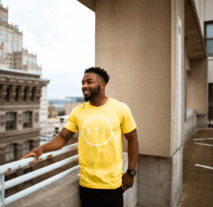 An African American man standing on a rooftop wearing a yellow STL T-shirt