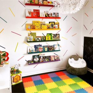 a colorful playroom with bookshelves, a multicolor playmat, and washi tape stripes on the walls