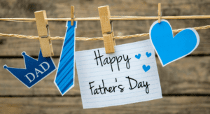 A clothesline with a clothespin holding a Happy Father's Day sign with a blue heart, a blue tie, and a crown that says Dad against a wooden slat background