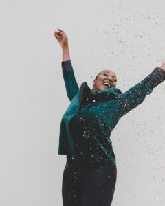 an African American woman with her arms up in the air as she tosses confetti