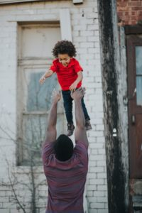 a black man lifting his son up in the air