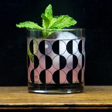 a cocktail glass with a sprig of mint coming out the top