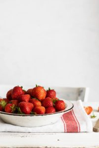 a white bowl filled with strawberries on a cloth dish towel on a white table to represent summer recipes you can make for dessert