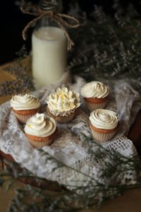 cupcakes with white icing on a cloth next to a white candle