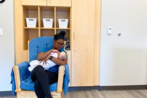 a childcare worker sitting in a blue rocker, holding a baby