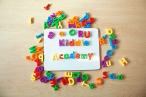 a white magnetic board with multicolor alphabet magnets scattered around the board as the letters on the board spell out Kiddie Academy