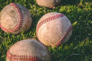 close up of baseballs in the grass