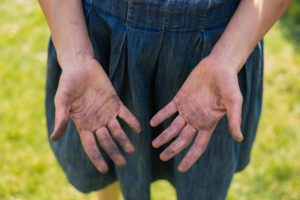 A young woman is showing of her dirty hands covered in dirt from gardening