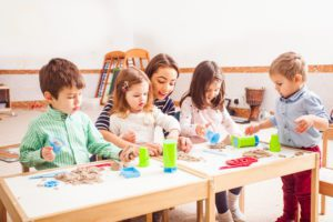 children sitting on the floor with a mommy's helper playing with kinetic sand