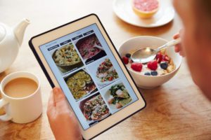 a close up of a woman eating breakfast as she scrolls on her tablet to find recipes
