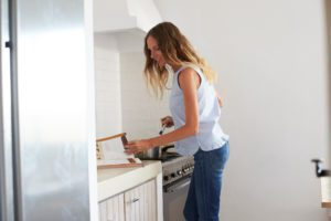 Woman reading recipe book and preparing food in kitchen