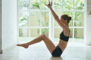 a woman in a yoga pose in front of a window