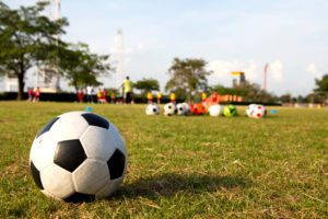 a close up of a soccer goal in the foreground and soccer gear is blurred in the background