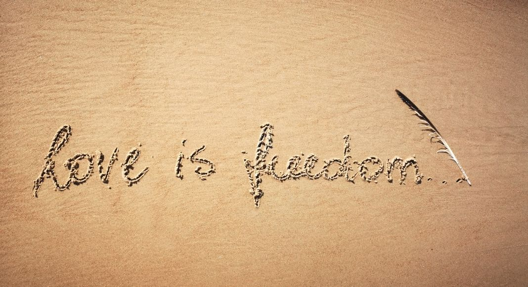 love is freedom written in the sand with a feather