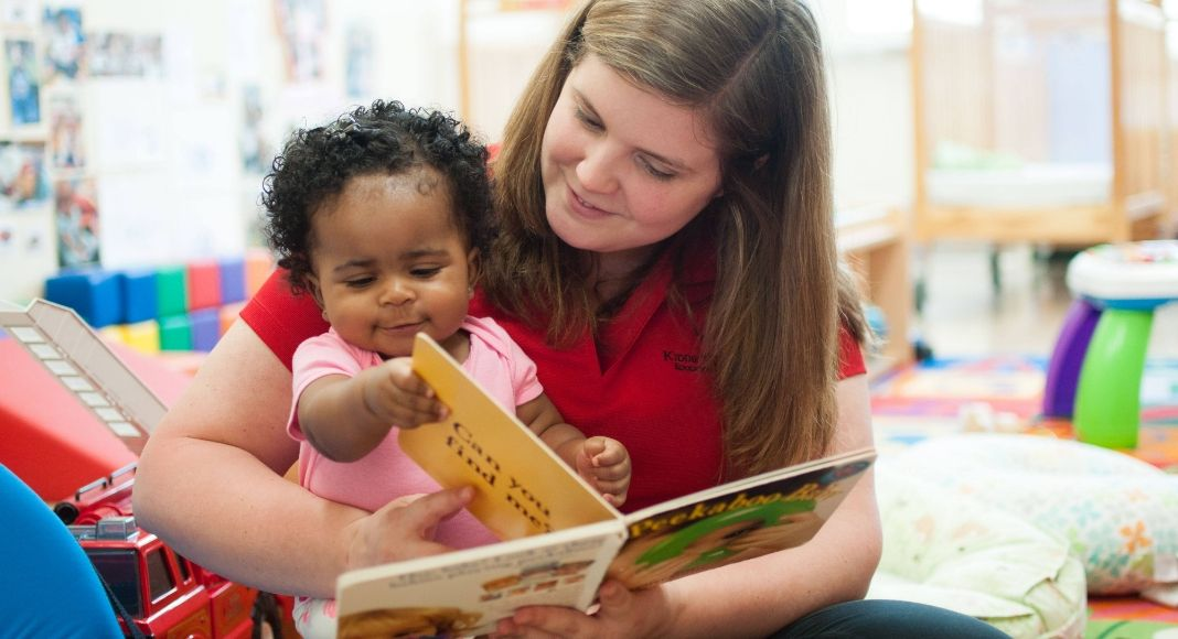 a childcare worker in a red shirt reading a board book to the infant in a pink shirt on her lap