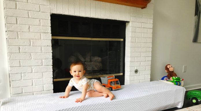 DIY hearth seat cover with a baby sitting on top of it