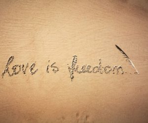 the words love is freedom written in the sand with a feather to symbolize love your body
