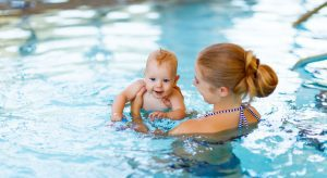 a mom and her baby taking in the pool taking swim lessons