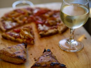 pizza on a cutting board with a glass of white wine