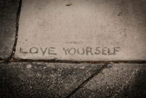 the words love yourself etched in a concrete sidewalk