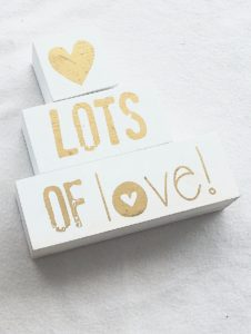 """white pieces of wood with a heart and the words, """"lots of love"""" painted on them in gold"""