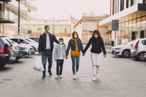a family walking in a parking lot, holding hands and wearing mask for COVID 19
