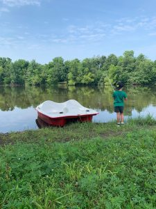 a boy standing next to a boat on a lake