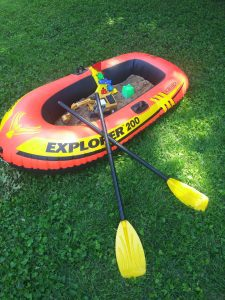 an inflatable boat filled with sand and toys in the backyard