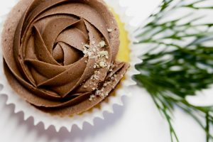 a yellow cupcake with chocolate icing on a white tabletop with sprigs of greenery