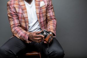 a close up of a Black-owned business man sitting as he holds a camera