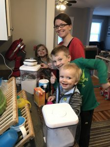 a mom with her three kids, and a counter strewn with baking supplies as she is cooking with kids