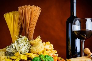 a glass of red wine in front of an uncorked wine bottle along with a variety of fresh made pastas